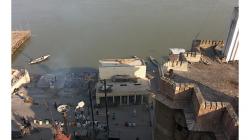 Varanasí - Pohled z balkonu hotelu Son Mony - u řeky stoupá dým z nebožtíka, stavba vpravo je moderní krematorium