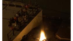Varanasí - rodina sleduje z laviček, jak před nimi hoří někdo příbuzný