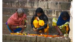 Varanasí - ranní očistná koupel v řece - chystání květů a svíček