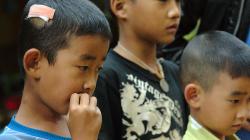 Děti uloveného hada pozorují z úctivé vzdálenosti